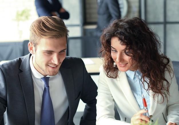 Бизнес-команда запуска на встрече в современном ярком интерьере офиса, мозговой штурм, работа над ноутбуком и планшетным компьютером