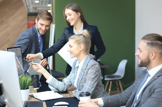 Команда запуска бизнеса на встрече в современном ярком интерьере офиса, мозгового штурма, работая на планшетах и компьютерах пк.