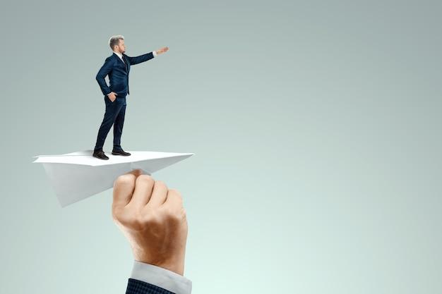 起動。投資家の手で紙飛行機で飛んでいるビジネスマン