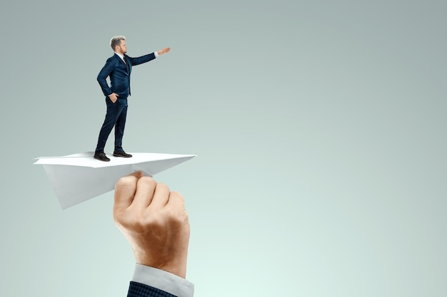 Startup. businessman flying on a paper airplane with the pushing hand of an investor