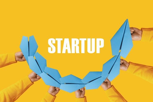 Startup concept, hands holding paper planes over yellow background