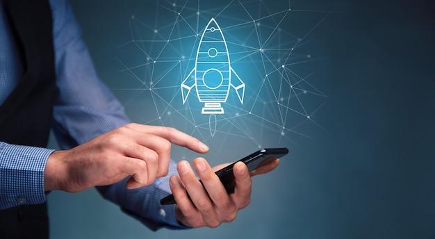 スタートアップのコンセプト、ロケットで携帯電話を持っている男