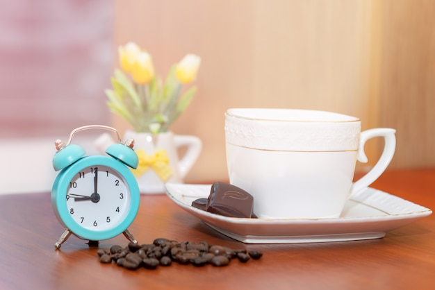 Startup concept. vintage alarm clock close-up start of a good day with a cup of coffee and a flower pot on the background in the morning sunlight.