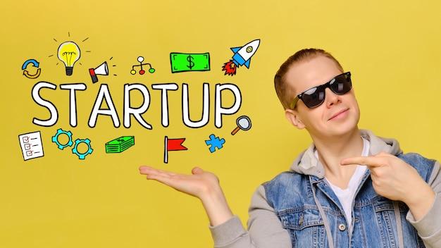 Startup концепция - молодой парень усмехаясь на желтом космосе.