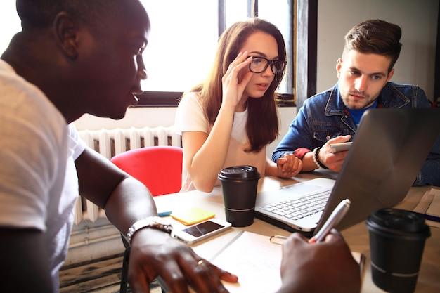 スタートアップの多様性チームワークブレーンストーミング会議のコンセプト。世界経済レポートドキュメントを共有するビジネスチームの同僚