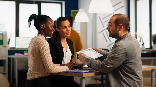 現代のオフィスの机に座ってブレーンストーミングを行い、タブレット検索管理ソリューションを保持するビジネス戦略を計画するスタートアップダイバーシティチームワーク。多民族のビジネスマンの働く会社のチーム