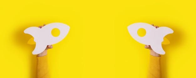 노란색 배경 위에 손에 시작 로켓, 텍스트를위한 공간이있는 파노라마 모형 이미지