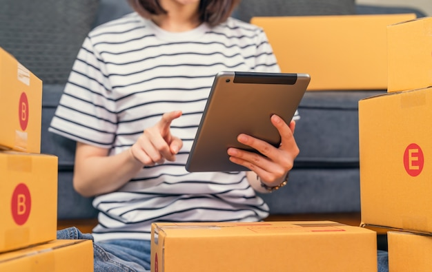 시작 중소 기업, 디지털 노트북 및 포장 상자에서 온라인 주문을 확인하는 젊은 아시아 여성