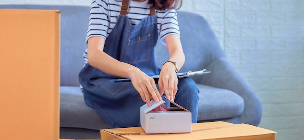 Startup small business concept, young asian woman owner working and packing on the box to customer at the sofa in home office, seller prepares the delivery.