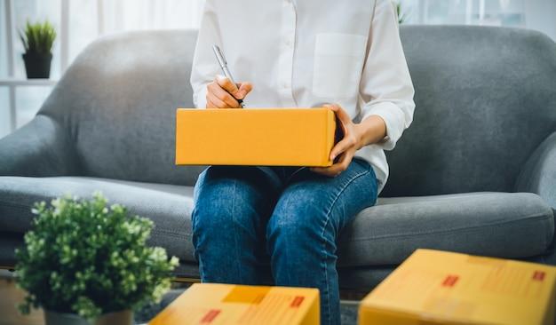 中小企業のスタートアップ、女性のオーナーがオンライン注文から顧客に商品を届ける梱包箱。