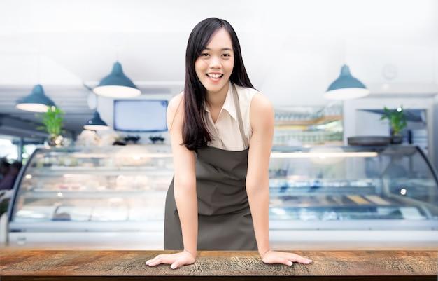 スタートアップ成功した中小企業のオーナーのsmeビューティーガールは、フードショップレストランのある木のテーブルの上に立っています。アジアの女性バリスタカフェビジネスコンセプトの肖像(パスを含む)