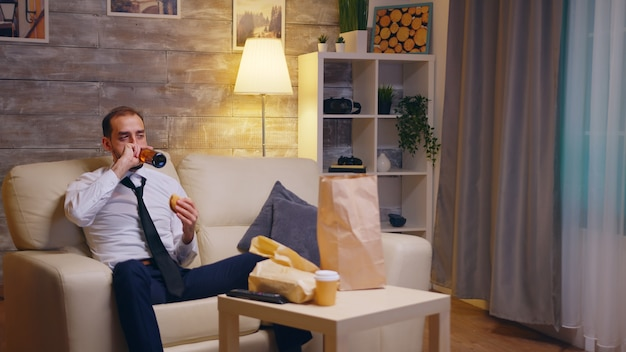 Uomo d'affari affamato in tuta dopo una lunga giornata di lavoro mangiando hamburger e usando il telecomando della tv. cibo malsano.