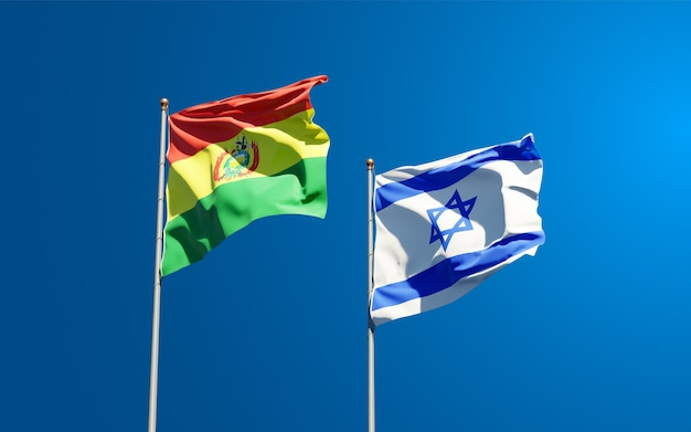 State flags of israel and bolivia together on sky background