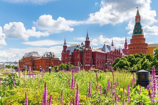 Государственный исторический музей и музей отечественной войны 1812 года с манежной площади в москве на фоне зеленых растений на лужайке солнечным летним утром