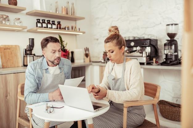事業の状態。台所のテーブルに座ってビジネスの状況について話し合う2人の集中カフェオーナー。