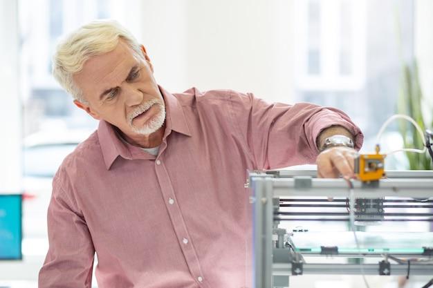 最先端の設備。オフィスで3dプリンターを使用し、その仕事を制御する魅力的な老人