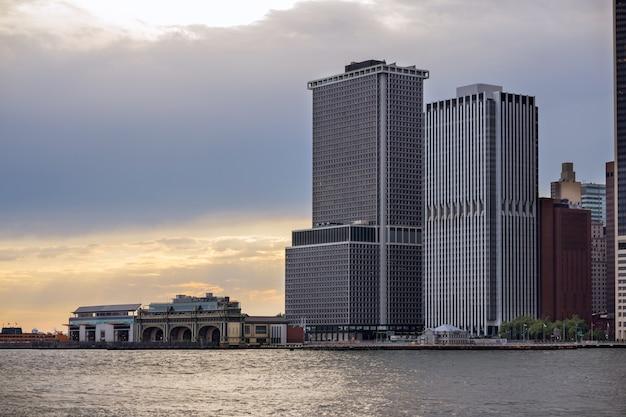 Паромный терминал статен-айленда в деловом районе нижнего манхэттена на фоне линии горизонта нью-йорка с современными небоскребами, офисные здания, светлый закат в общественном транспорте, лодка на якоре