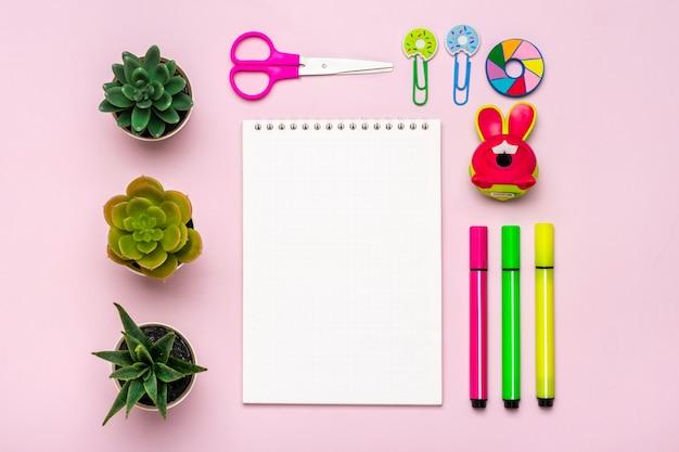 고정식, 학교로 돌아가기, 여름 시간, 창의성 및 교육 개념 학교 용품 - 돋보기, 연필, 펜, 종이 클립, 스테이플러 및 메모장을 분홍색 배경에 평평하게 놓고 위쪽 보기를 모의합니다.
