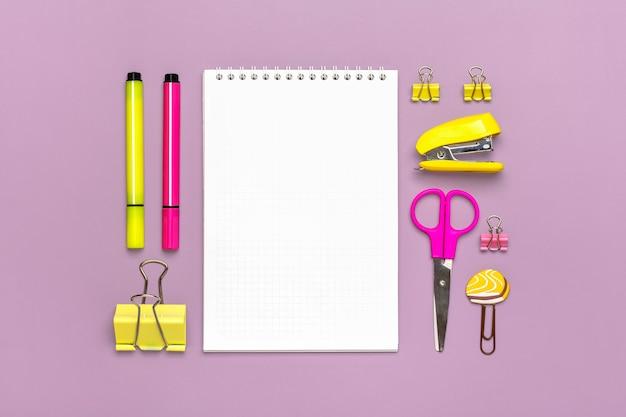 고정식, 학교로 돌아가기, 여름 시간, 창의성 및 교육 개념 학교 용품 - 돋보기, 연필, 펜, 종이 클립, 스테이플러 및 메모장을 보라색 배경에 평평하게 놓고 위쪽 보기를 모의합니다.