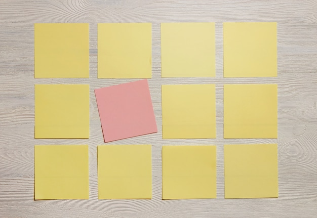 Stationary, blank colored sticker notes on white wooden board.