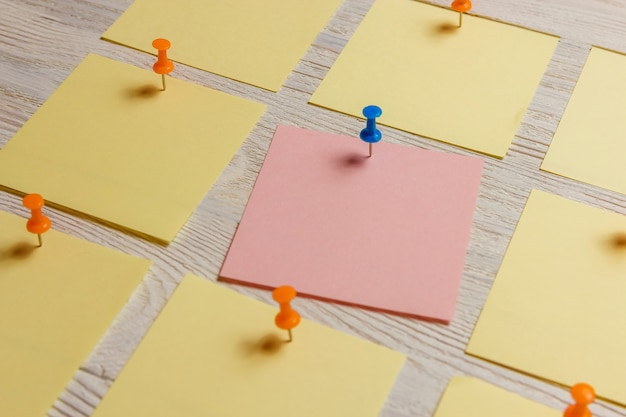 Stationary, blank colored sticker pined on white wooden board.