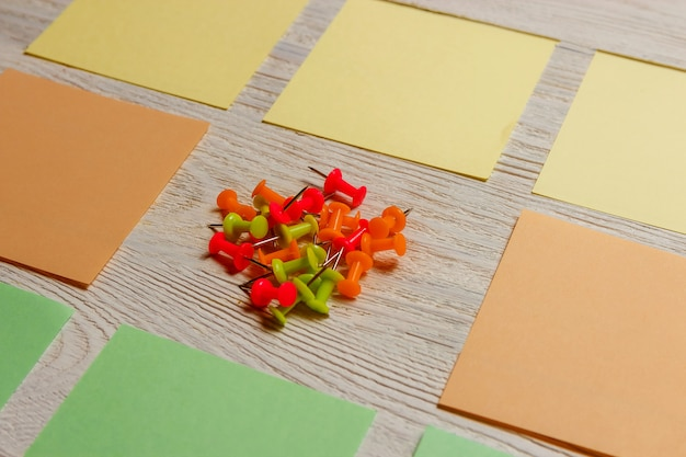 Stationary, blank colored sticker, pushpins heap on white wooden board.