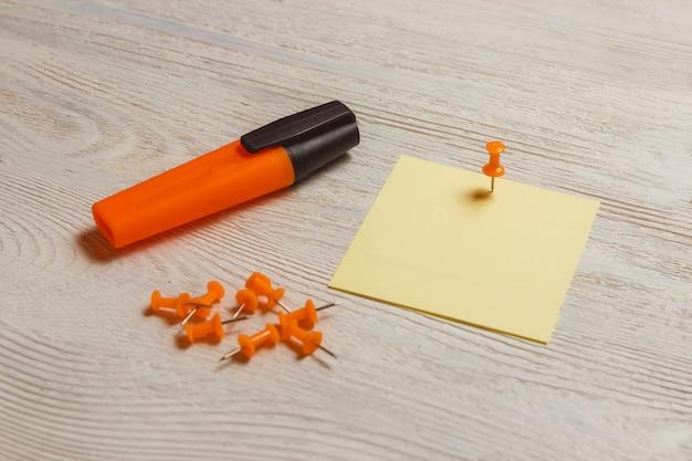 静止した、空白の黄色いステッカー、オレンジ色のプッシュピン、白い木の板のマーカー。