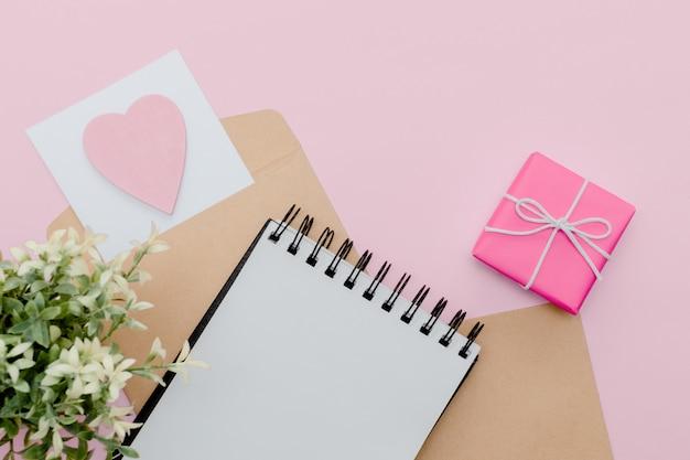 文房具のコンセプト、鉛筆、ペン、コピースペース、最小限のピンクの抽象的なテーブルでメモ帳