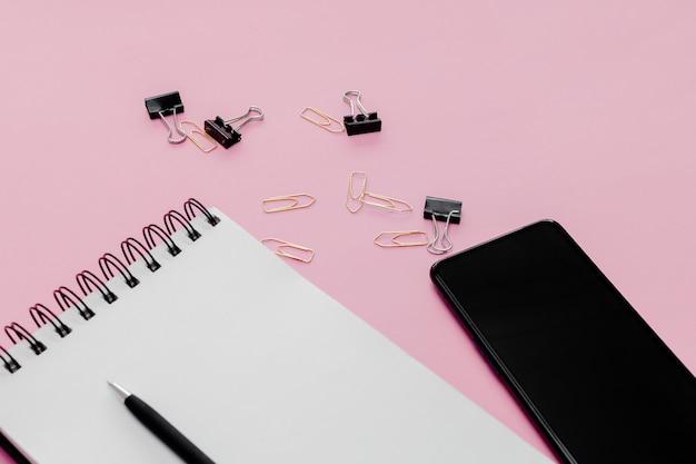 静止した概念、鉛筆、ペン、ピンクの抽象的なテーブルでメモ帳