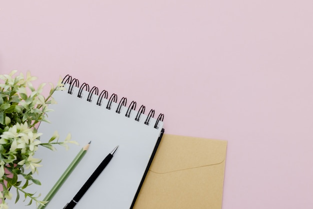 Stationary concept,  pencil, pen  and notepad  on a pink abstract table with copy space, minimal