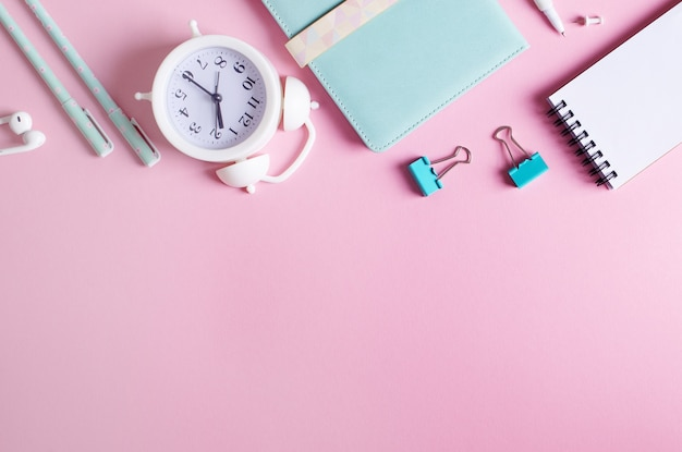 Stationary concept, top view flat lay photo of pencils, paper clips, alarm clock, notepads, in white and blue on pink background with copy space.