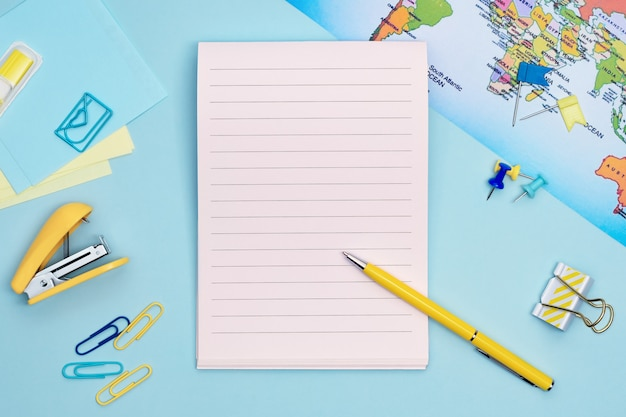 Stationary items, map and notebook for travel planning on blue background. traveling reminder flat lay concept with copy space.