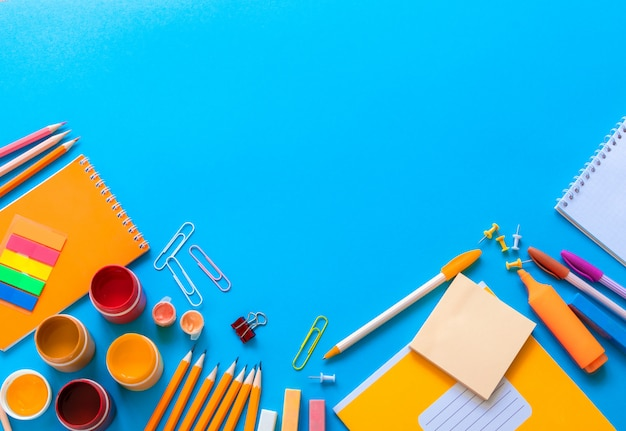 Stationary for school on blue background in flat lay design