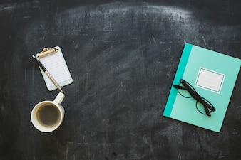 Stationeries and coffee cup on blackboard