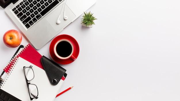 Канцелярские товары, очки, яблоко, ноутбук, наушники и кактус на столе