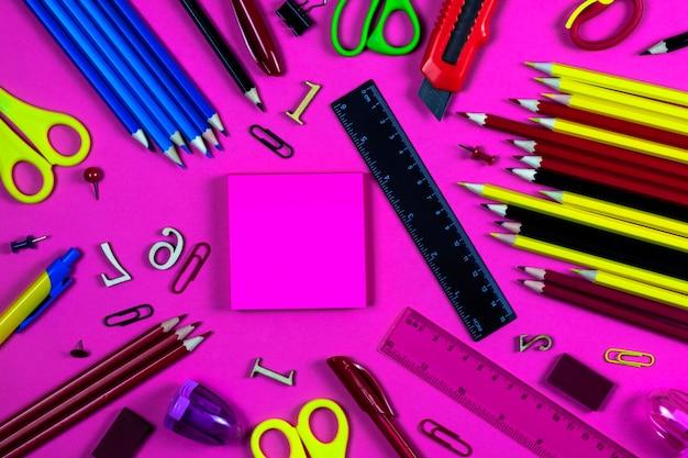 Канцелярские товары для школы и офиса лежат на розовом фоне с местом для текста.