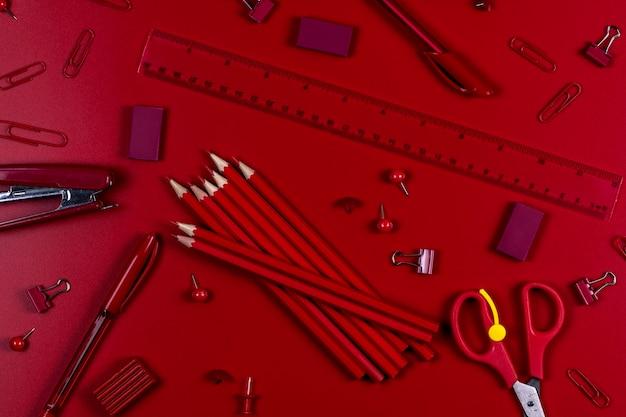Канцелярские товары для школы и офиса красного цвета лежат на красном фоне.