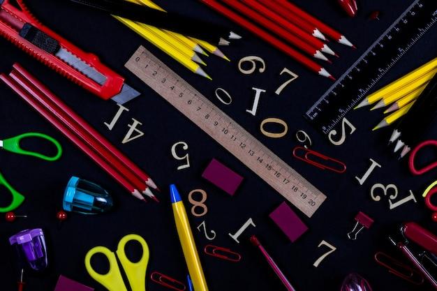 Канцелярские принадлежности разных цветов для школы и офиса лежат на черном фоне.