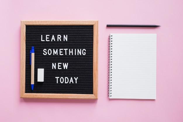 문구류는 분홍색 배경 위에 슬레이트에 새로운 오늘의 텍스트를 배웁니다.
