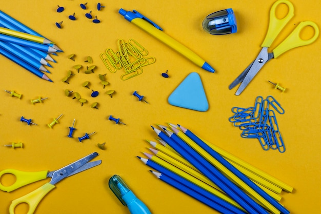 Канцелярские товары: желтые и синие карандаши, пуговицы, скрепки и ножницы, ручка и резинка лежат на желтом фоне.