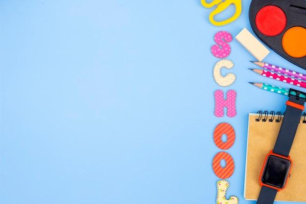 Аксессуар канцелярских принадлежностей на синем фоне. школьные принадлежности, карандаши, краски и цветные книги на синем фоне с копией пространства. концепция работы образования и фрилансера
