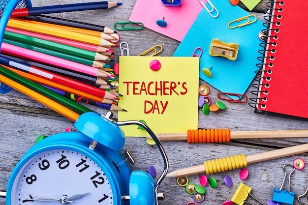 Канцелярские товары и будильник. день учителя - национальный праздник.
