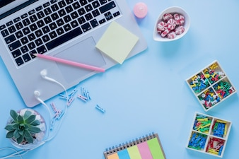 Stationery and candies near laptop and earphones