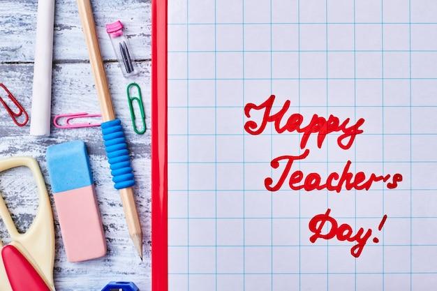Канцелярские товары и поздравительная надпись. выразите свое уважение учителю.