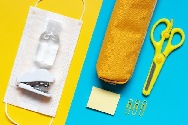 Канцелярские товары и медицинская маска на желтом и синем фоне вид сверху