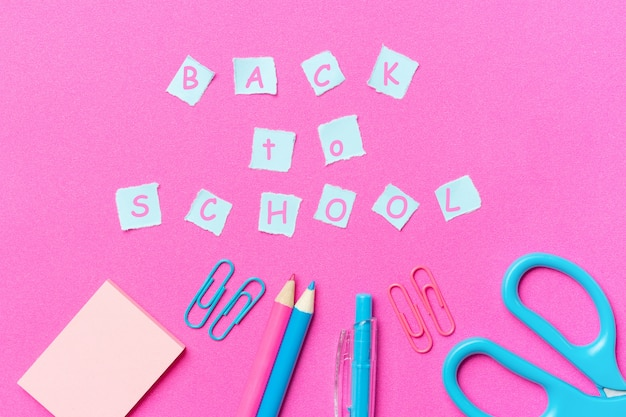 Канцтовары и надпись обратно в школу, розовый фон