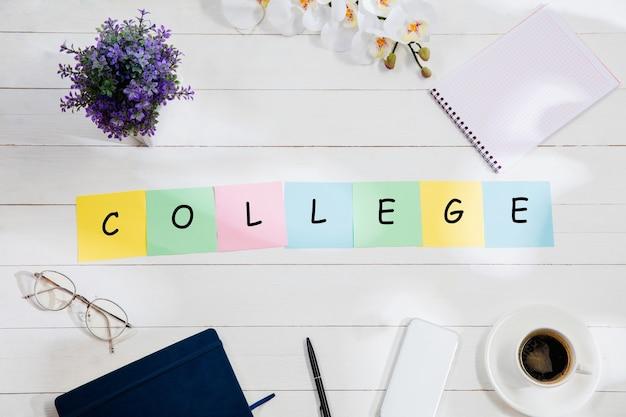 Канцелярские товары и слово колледж из букв на деревянных фоне. образование, колледж, школа