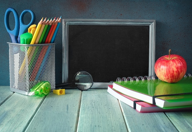Stationery, apple and banana on a wooden table in front of blackboard with text