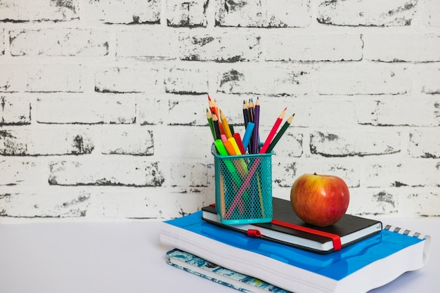 Stationery and apple laid on notebooks