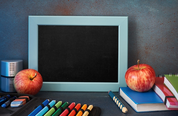 Stationery, apples and books  on wooden table in front of blackboard with text space